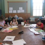 Campers coloring their tangram boards before cutting