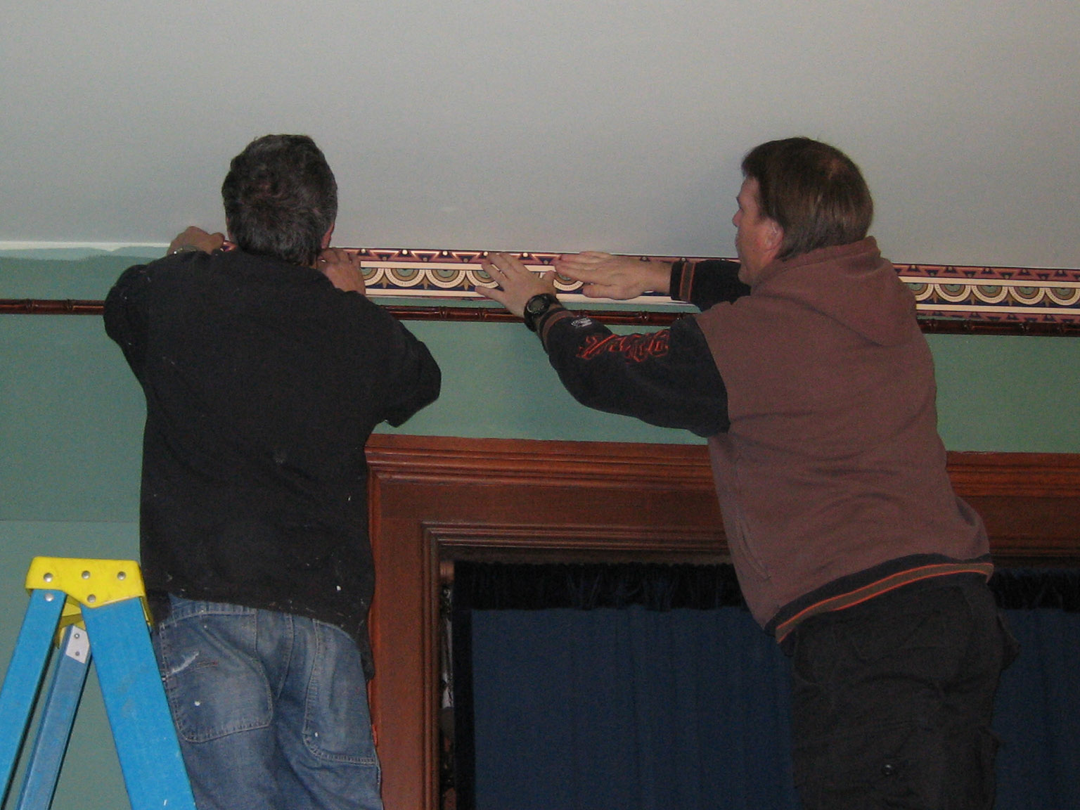 Volunteers Scott Broadwell and Tim Cowling hanging the reproduction historic wallpaper border.