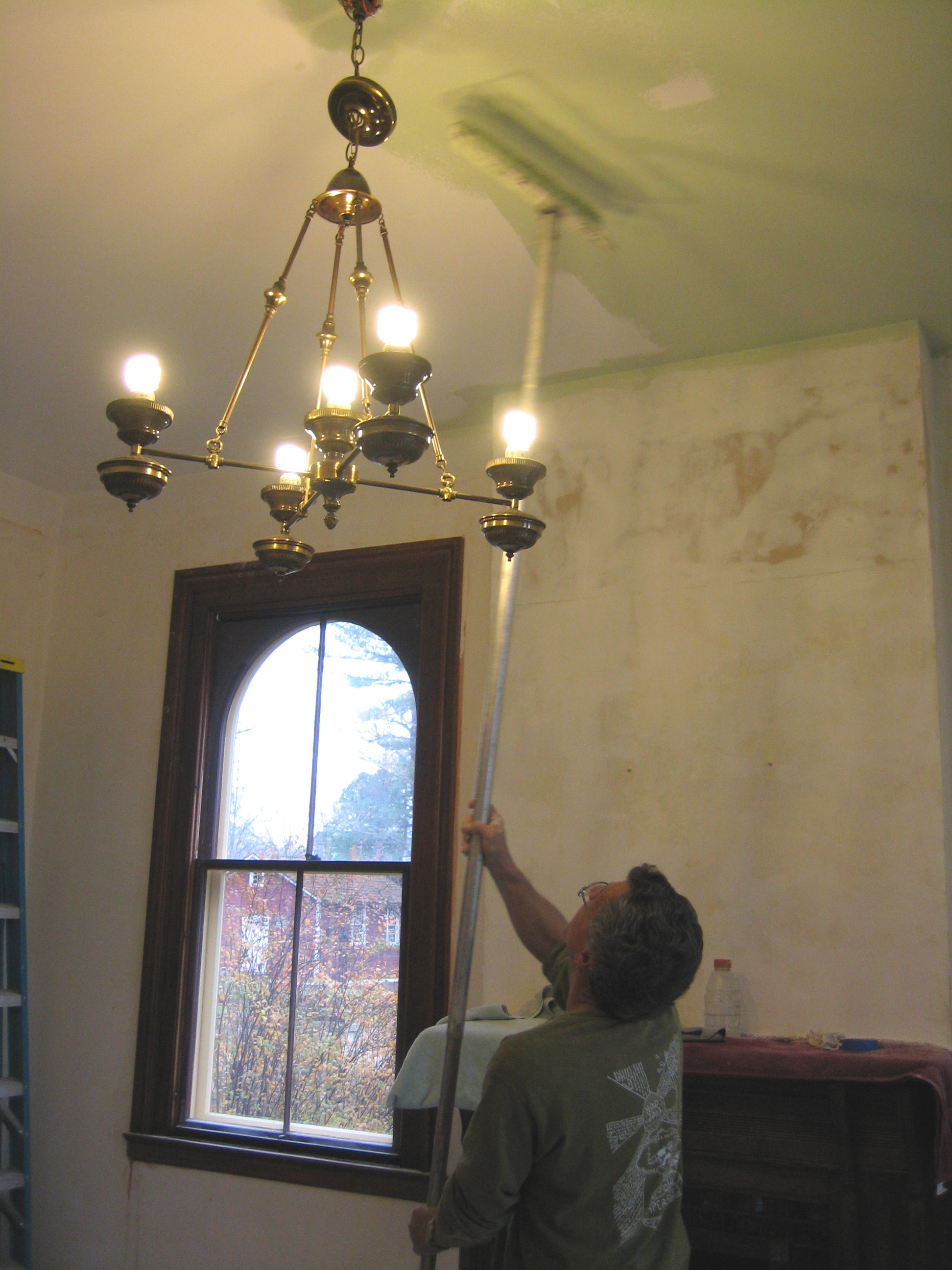 Volunteer Scott Broadwell painting the ceiling in the parlor.